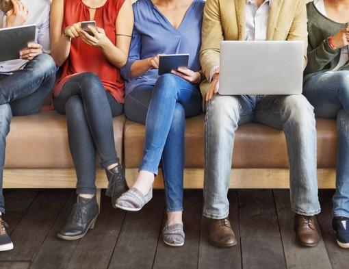Persone sedute alle prese con dispositivi digitali