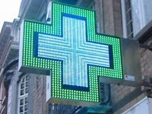 L'insegna luminosa di una farmacia a forma di croce